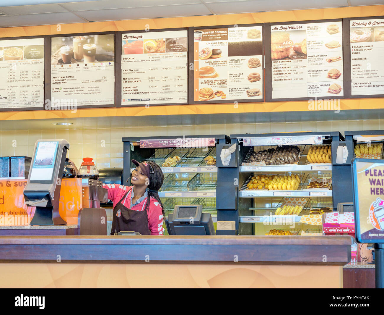 Female African-American fast food worker at the counter of Dunkin Donuts in Montgomery, Alabama United States. Stock Photo