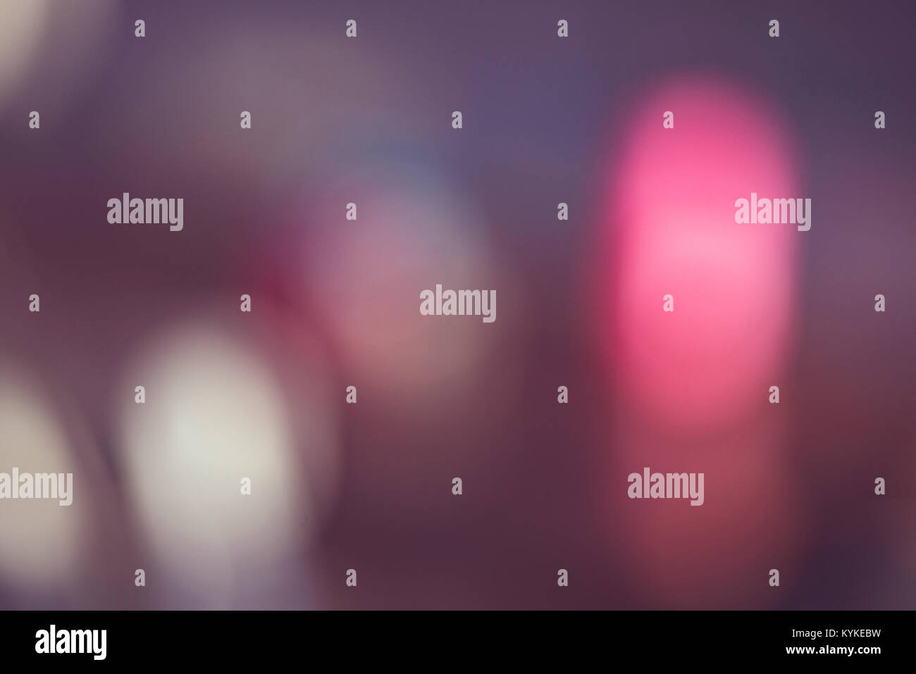 Blurry violet background with abstract pink lights out of focus in the dark - Stock Image