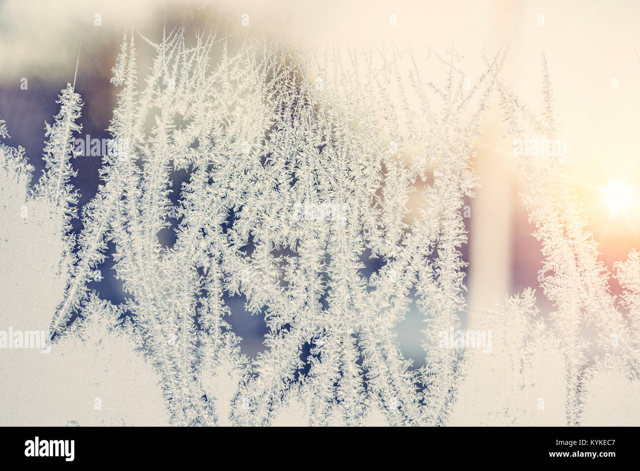 Sunrise behind a frosty window with beautiful frost patterns in the morning - Stock Image