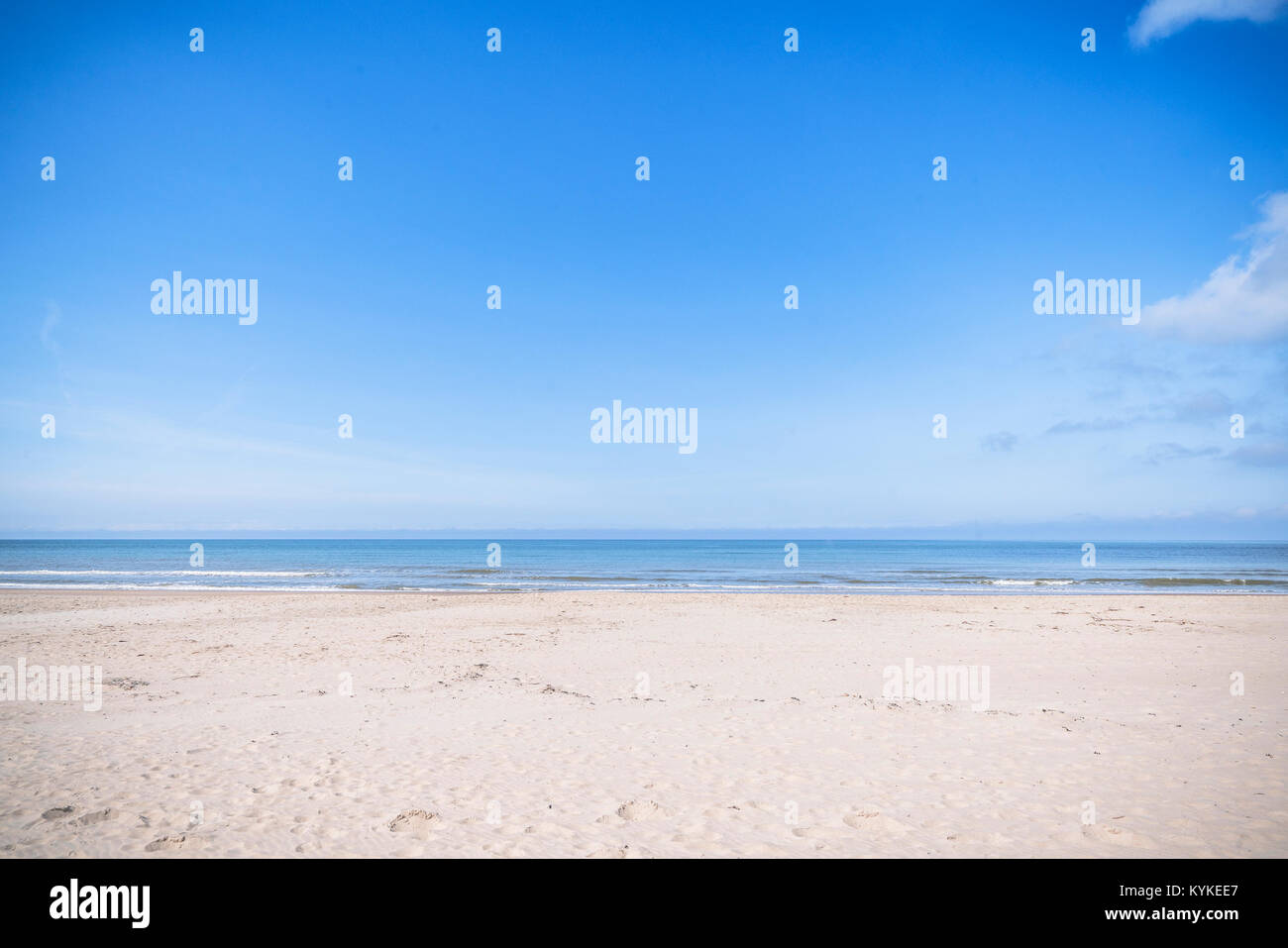 Empty beach by the sea in the summer with blue sky and dry sand - Stock Image