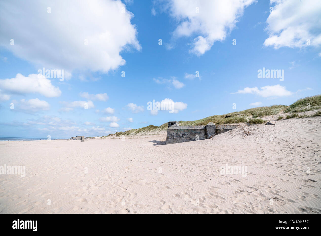 Danish beach with ruins of german bunkers from the 2nd word war in the summer with white clouds in the blue sky - Stock Image