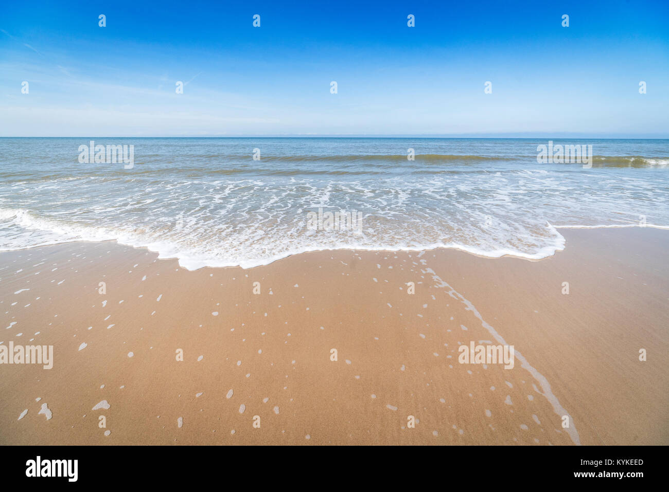 Beach with small waves coming in on the shore of a Scandinavian seaside - Stock Image