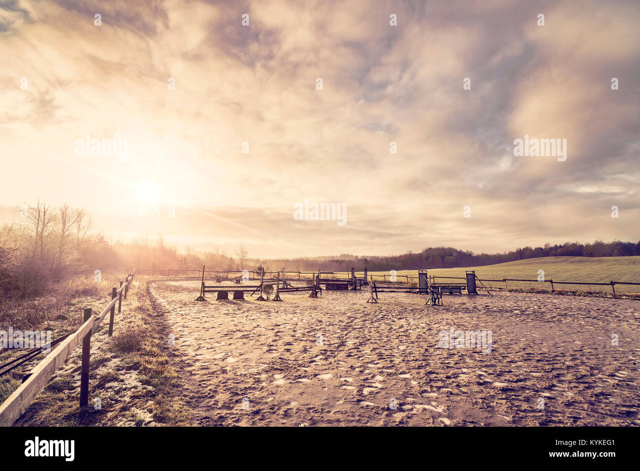 Horse equestrian course in the morning sunrise with frost on the muddy ground - Stock Image