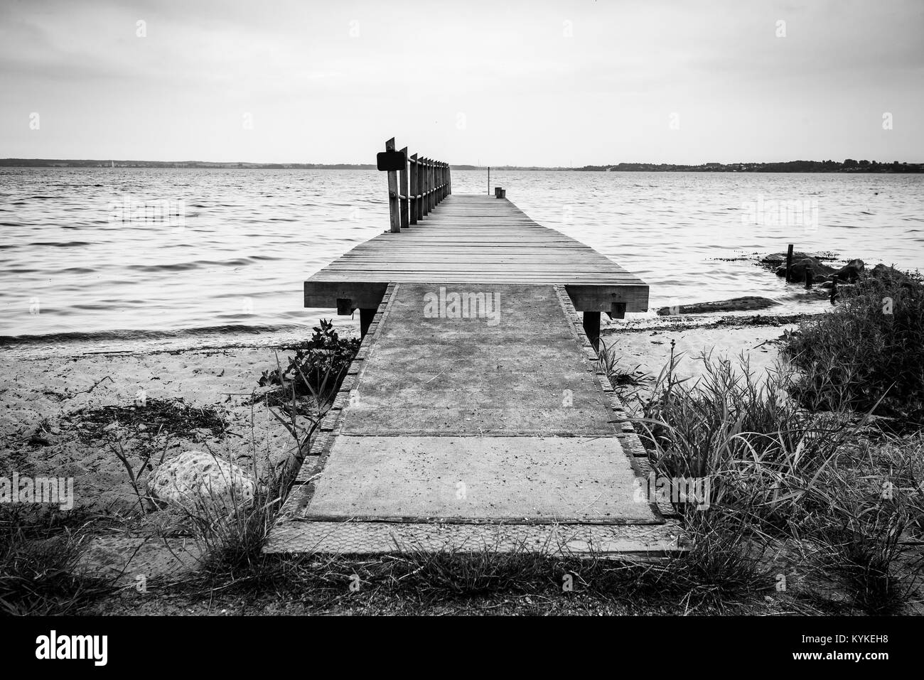 Wooden pier by the sea on a nordic beach in cloudy weather in black and white colors - Stock Image
