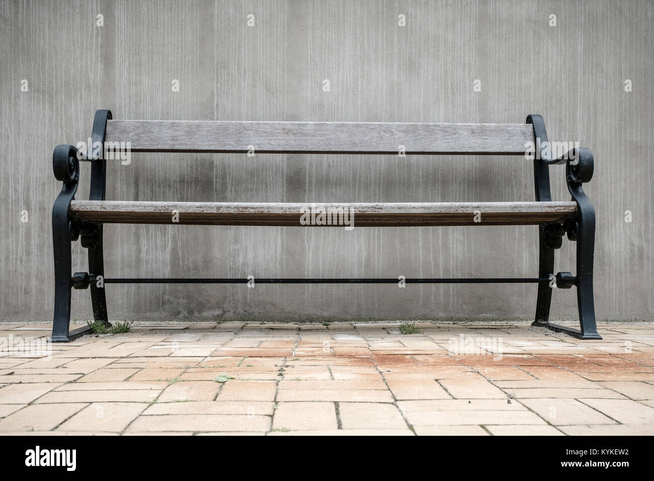 Wooden bench in vintage style on a terrace with a large concrete wall - Stock Image