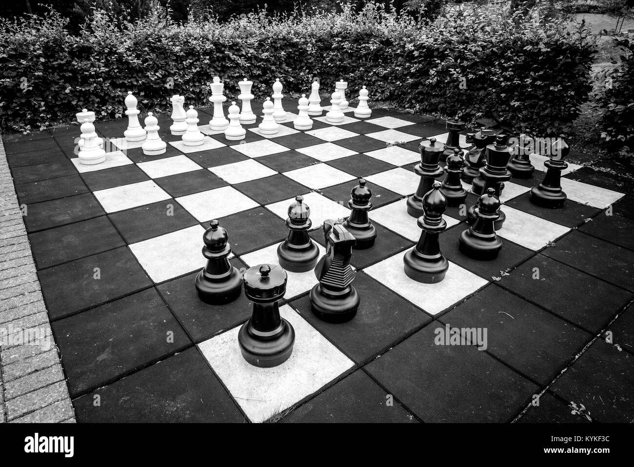 Chess game with large pieces in an outdoor version of the classic game in black and white colors - Stock Image