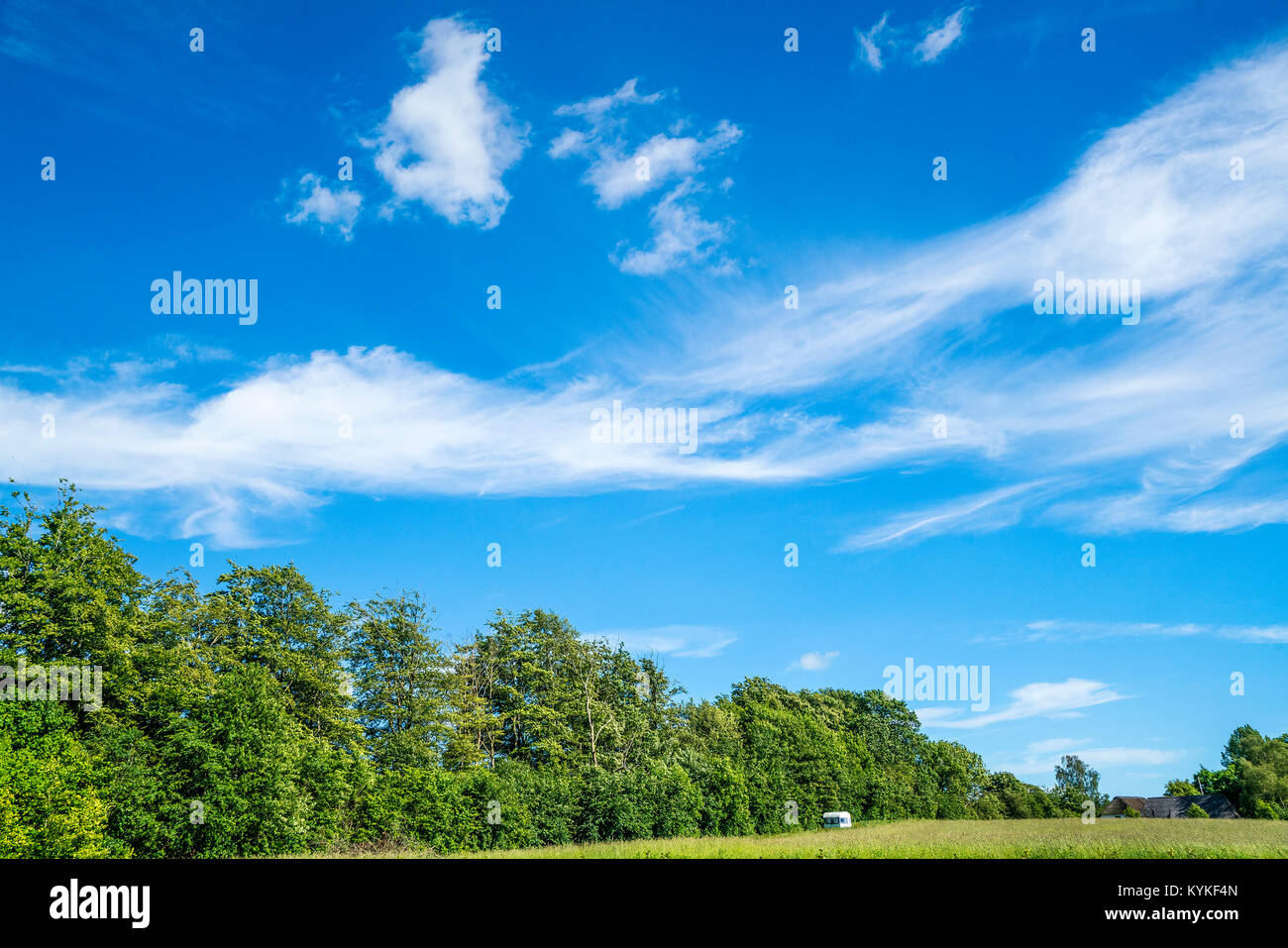 Camping trailer on a green field with blue sky in the summer - Stock Image