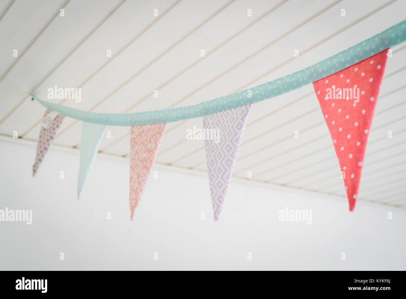 Colorful birthday flags in pastel colors hanging from a ceiling in bright playroom - Stock Image