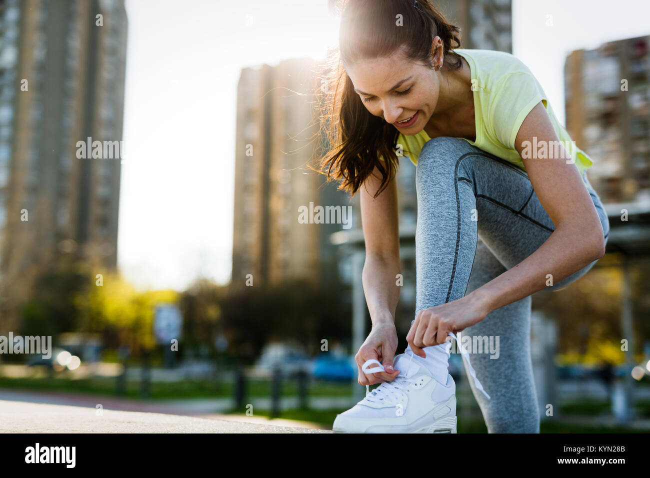 Attractive sportswoman tying shoelace and getting ready for fitness - Stock Image