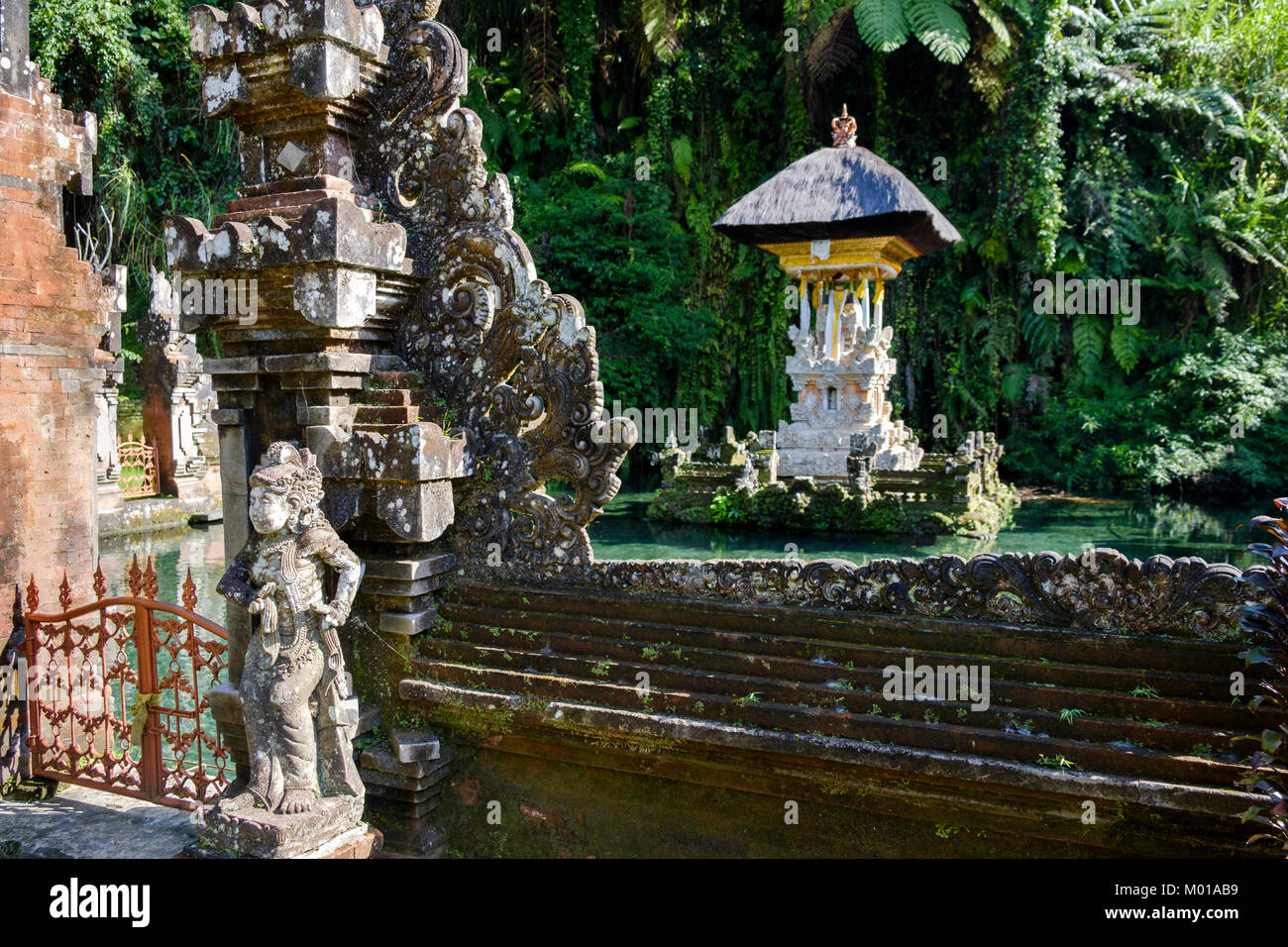 Statue and 'candi bentar' (split gate) with pond shrine at Pura Gunung Kawi Sebatu, a temple near Ubud, - Stock Image
