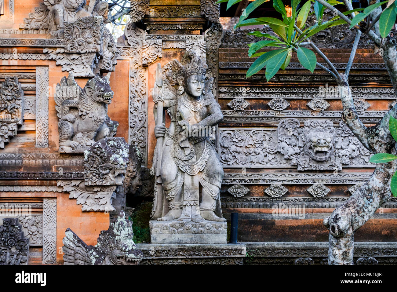 Stone carvings and statue on the outer wall of a Balinese compound in Ubud, Bali, Indonesia. - Stock Image