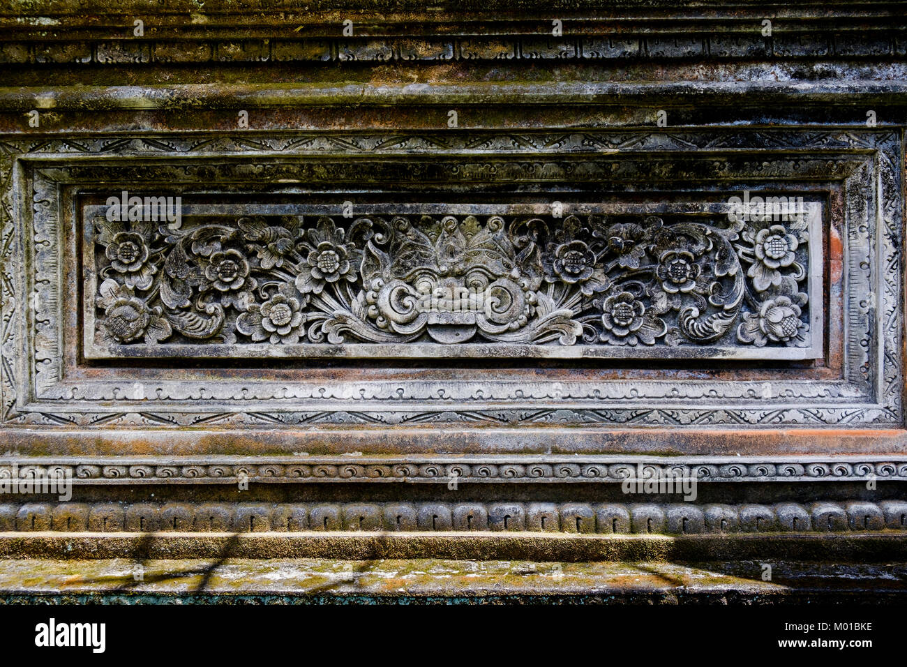 Stone-carved ornaments on wall of a Balinese-style house in Ubud, Bali, Indonesia - Stock Image