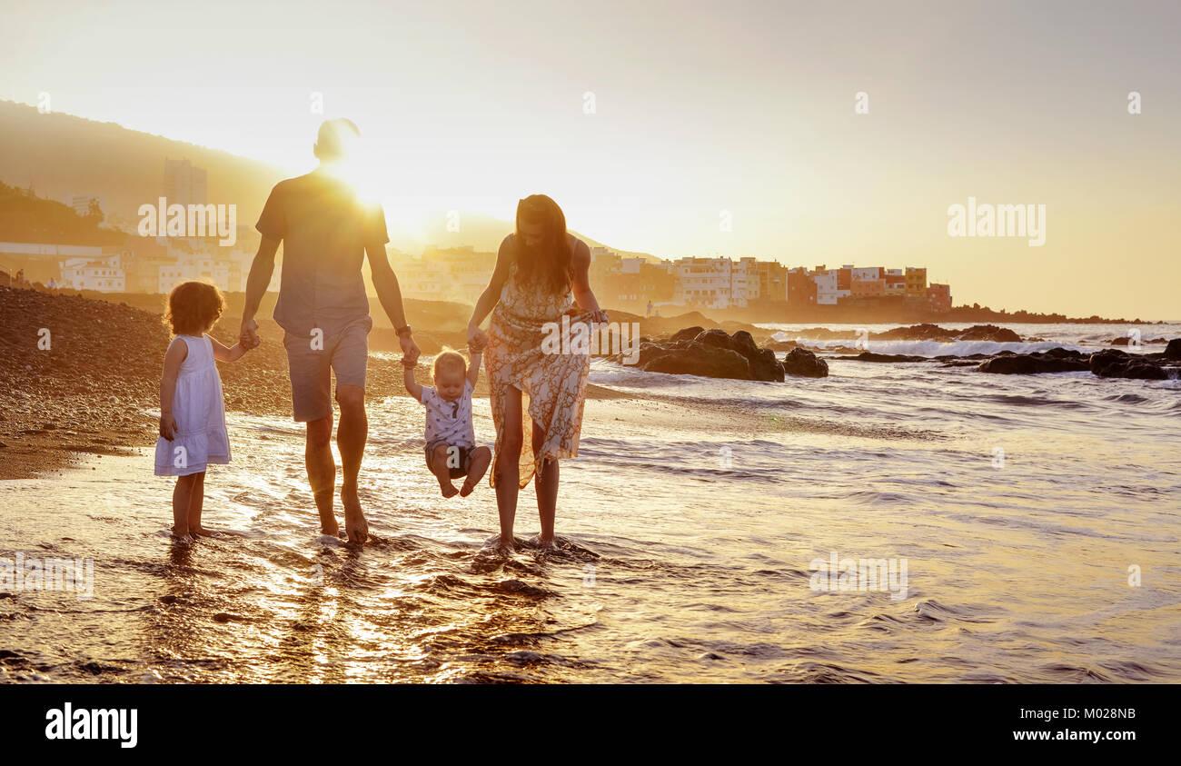 Joyful family having fun on a beach, summer portrait - Stock Image