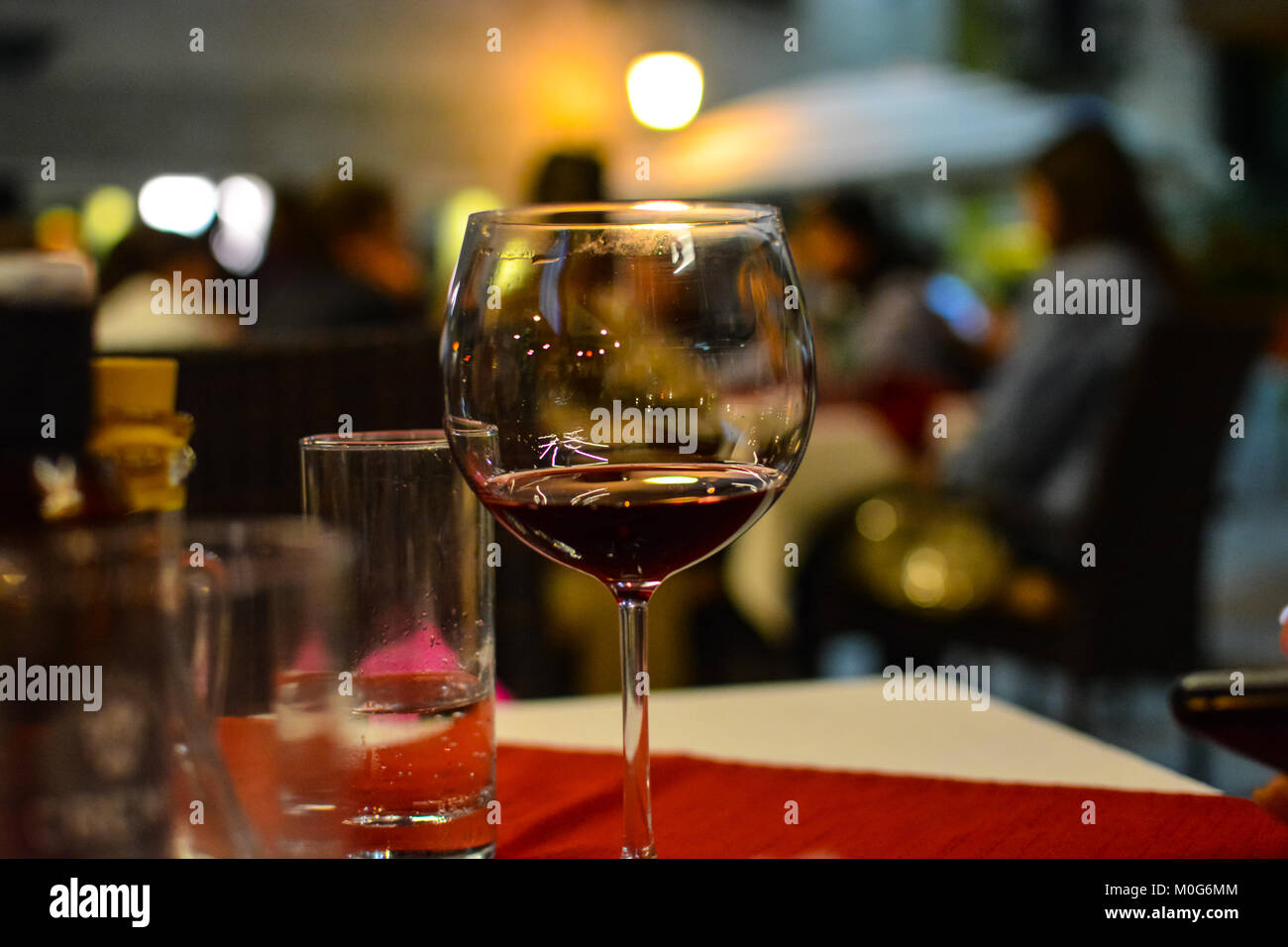 A half empty glass of wine sits on the table of a sidewalk cafe in Split Croatia - Stock Image