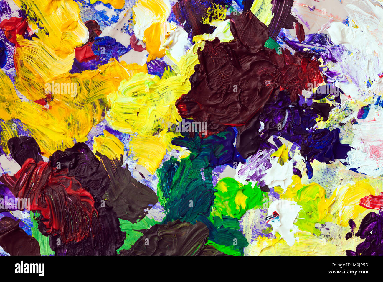 Bright palette of artist, texture of mixed oil paints in different colors, contrasting mix stains, splashes, texture - Stock Image