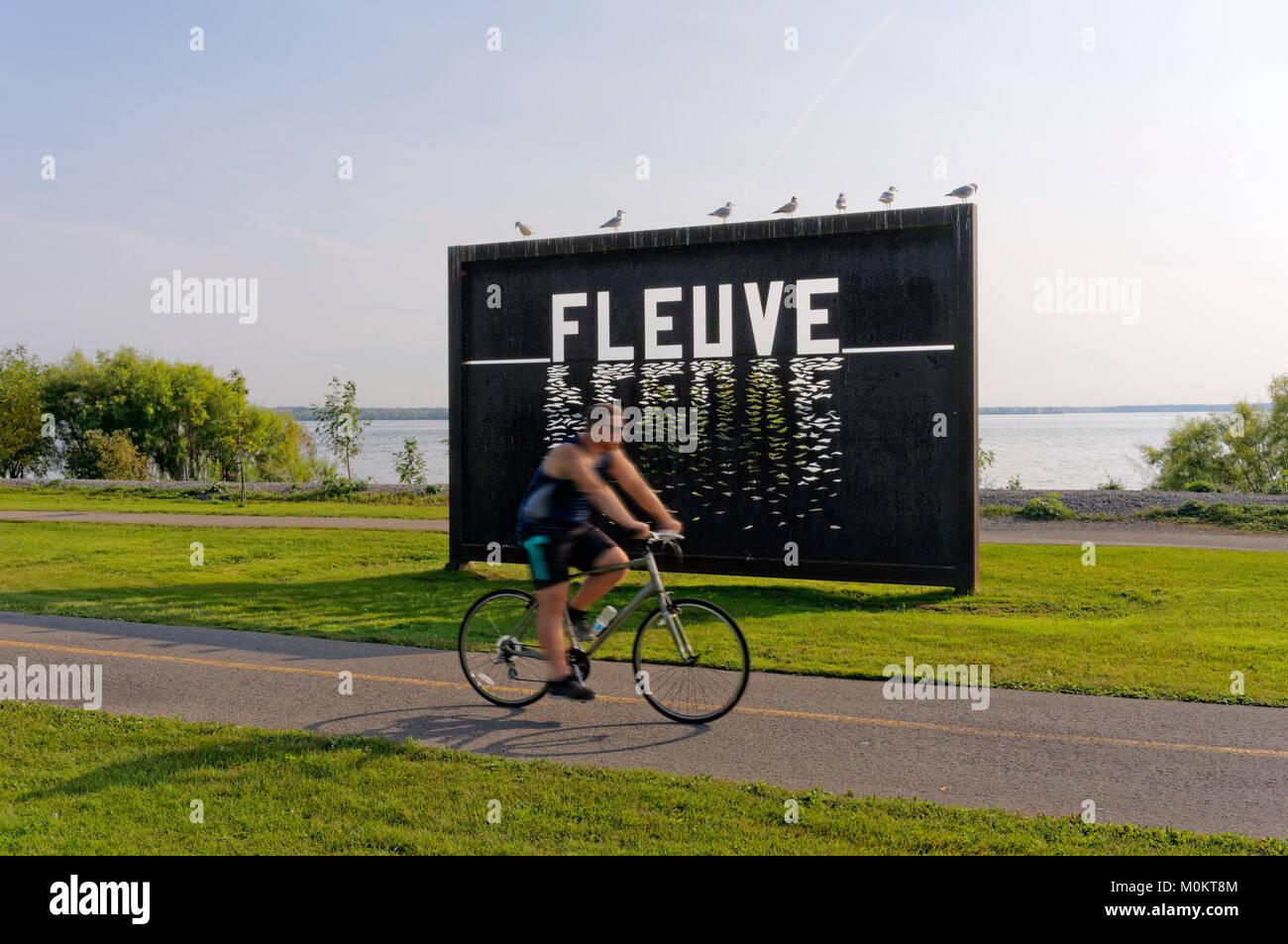 man-riding-a-bicycle-past-large-metal-pa