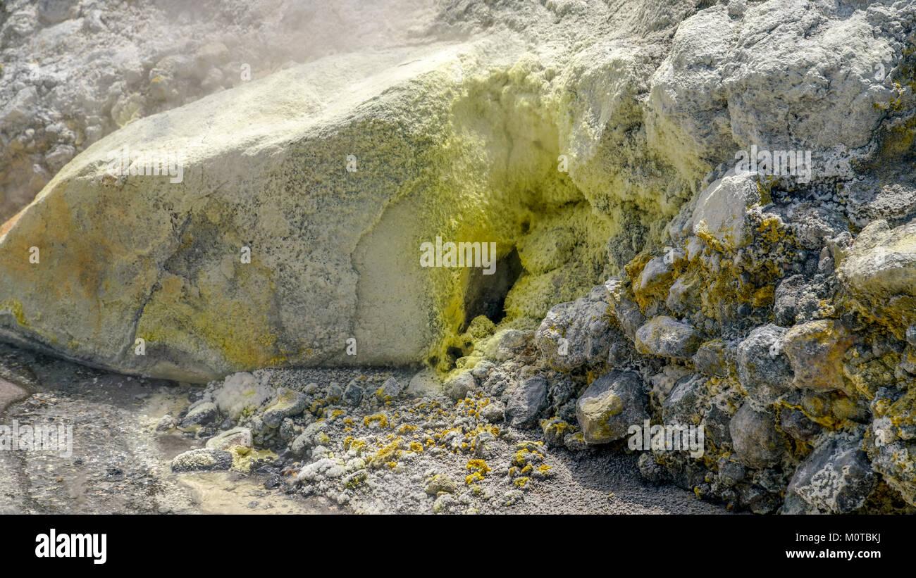 A fumarole is visible between puffs of sulphur smoke. White Island / Whakaarian volcano, Bay of Plenty, New Zealand - Stock Image