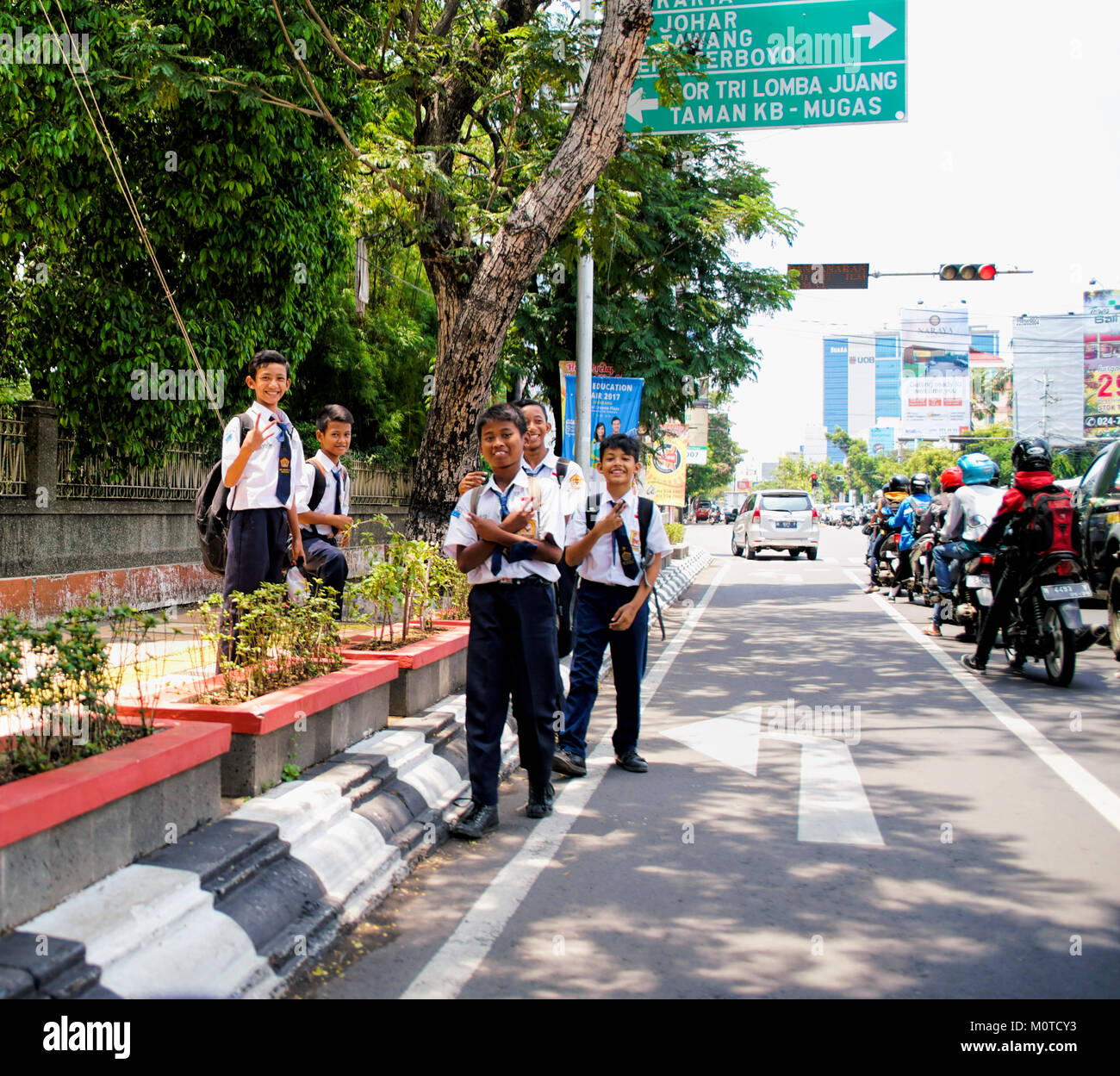 Javanese school boys laugh and smile as they walk along the busy street. Samarang, Java, Indonesia - Stock Image