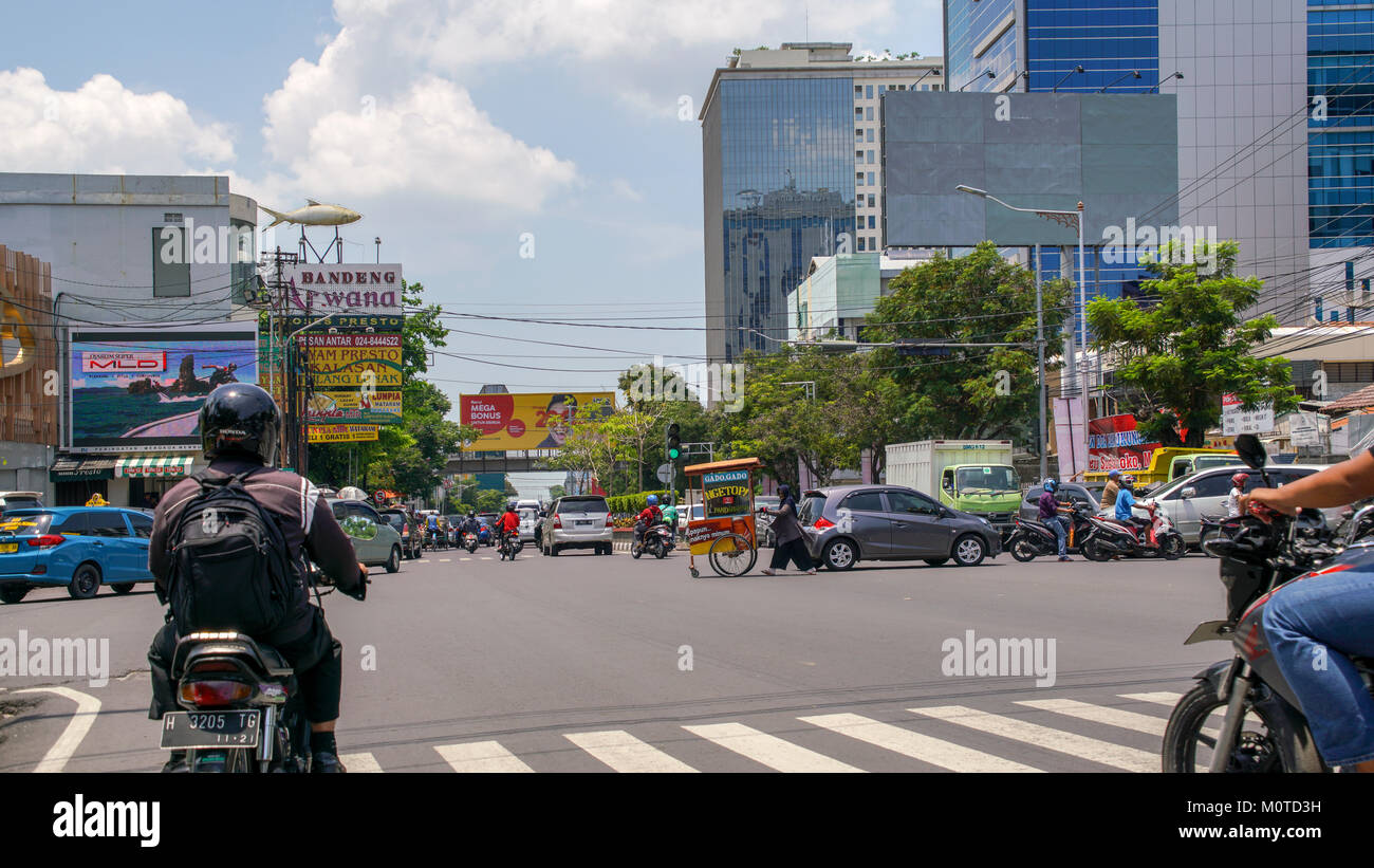 A woman pushes a foodcart down the middle of the street at a busy intersection. Semarang, Java, Indonesia. - Stock Image