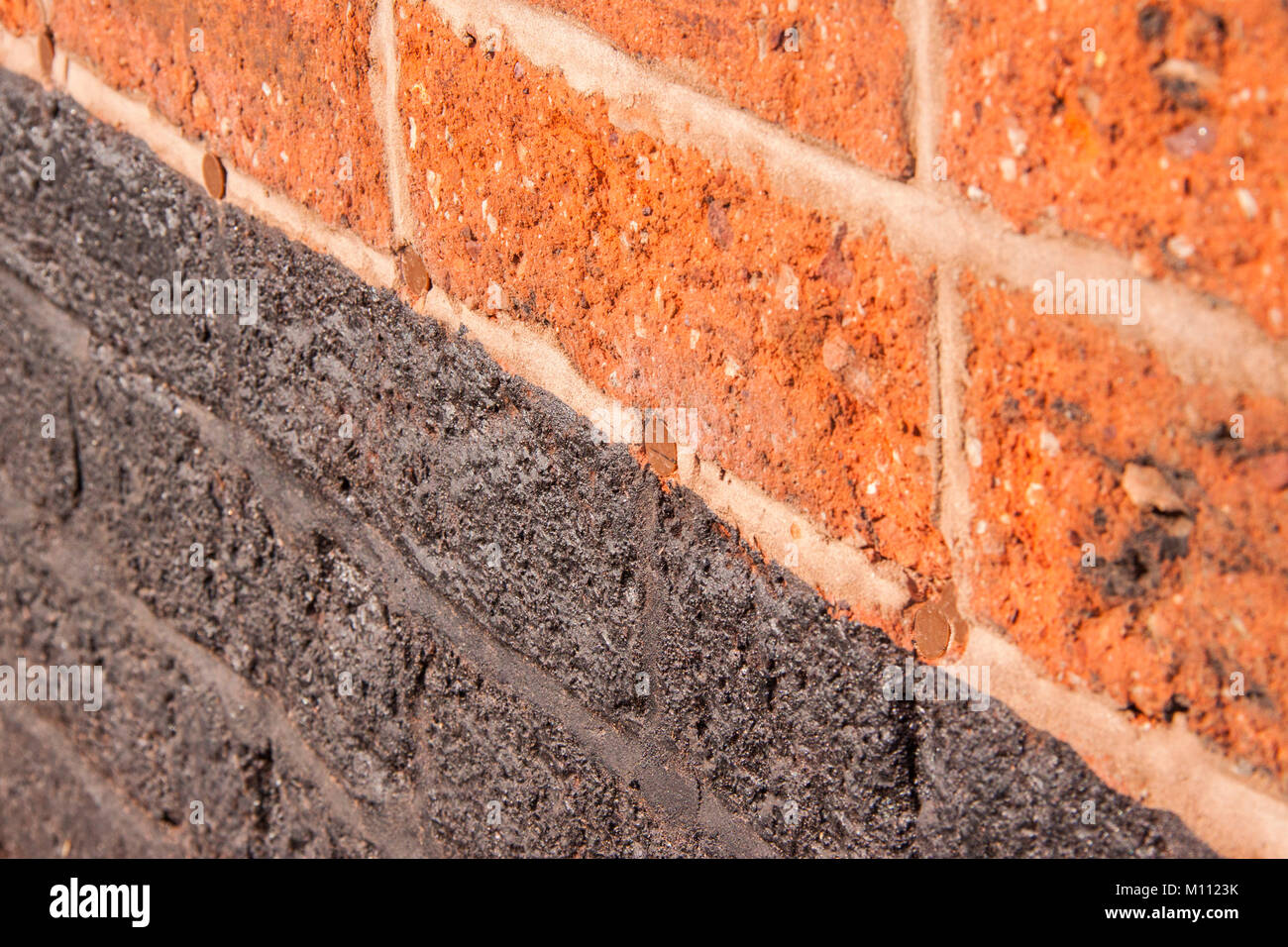 Red brick wall showing holes filled over after a damp proof course was injected into the brickwork. Stock Photo