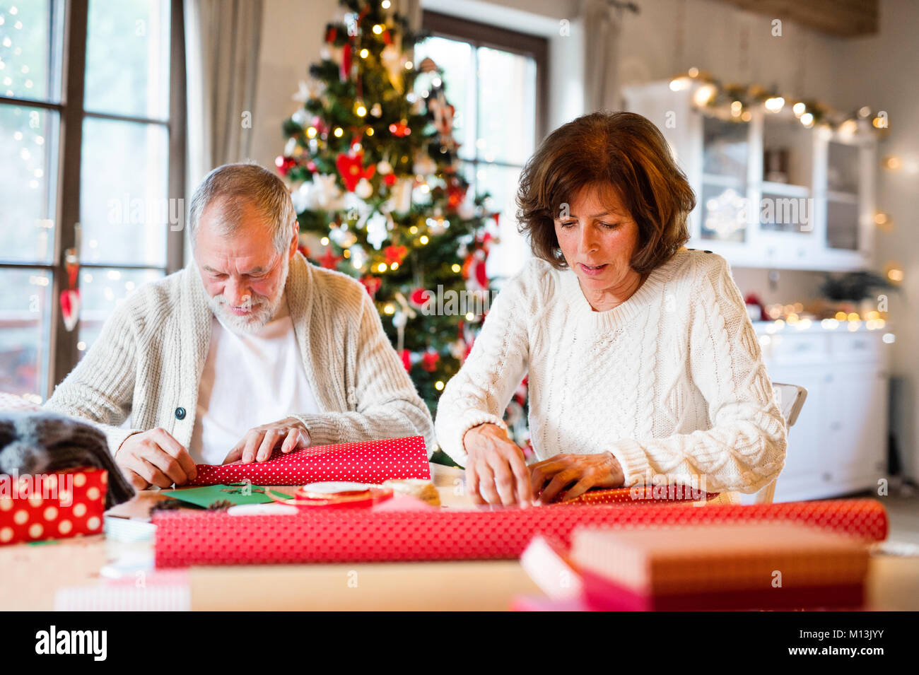senior couple in sweaters wrapping christmas gifts together