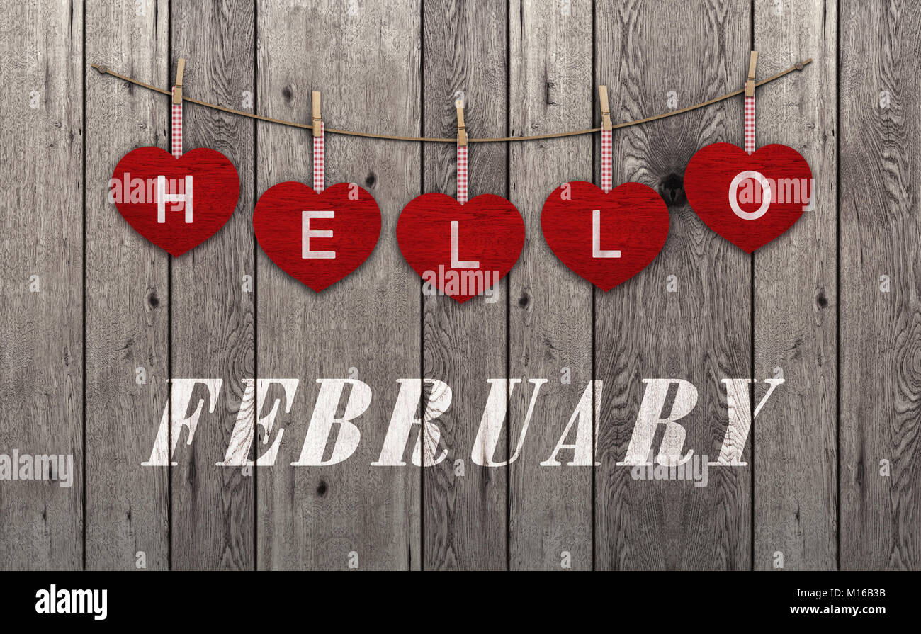 Hello february written on hanging red hearts and weathered wooden background - Stock Image