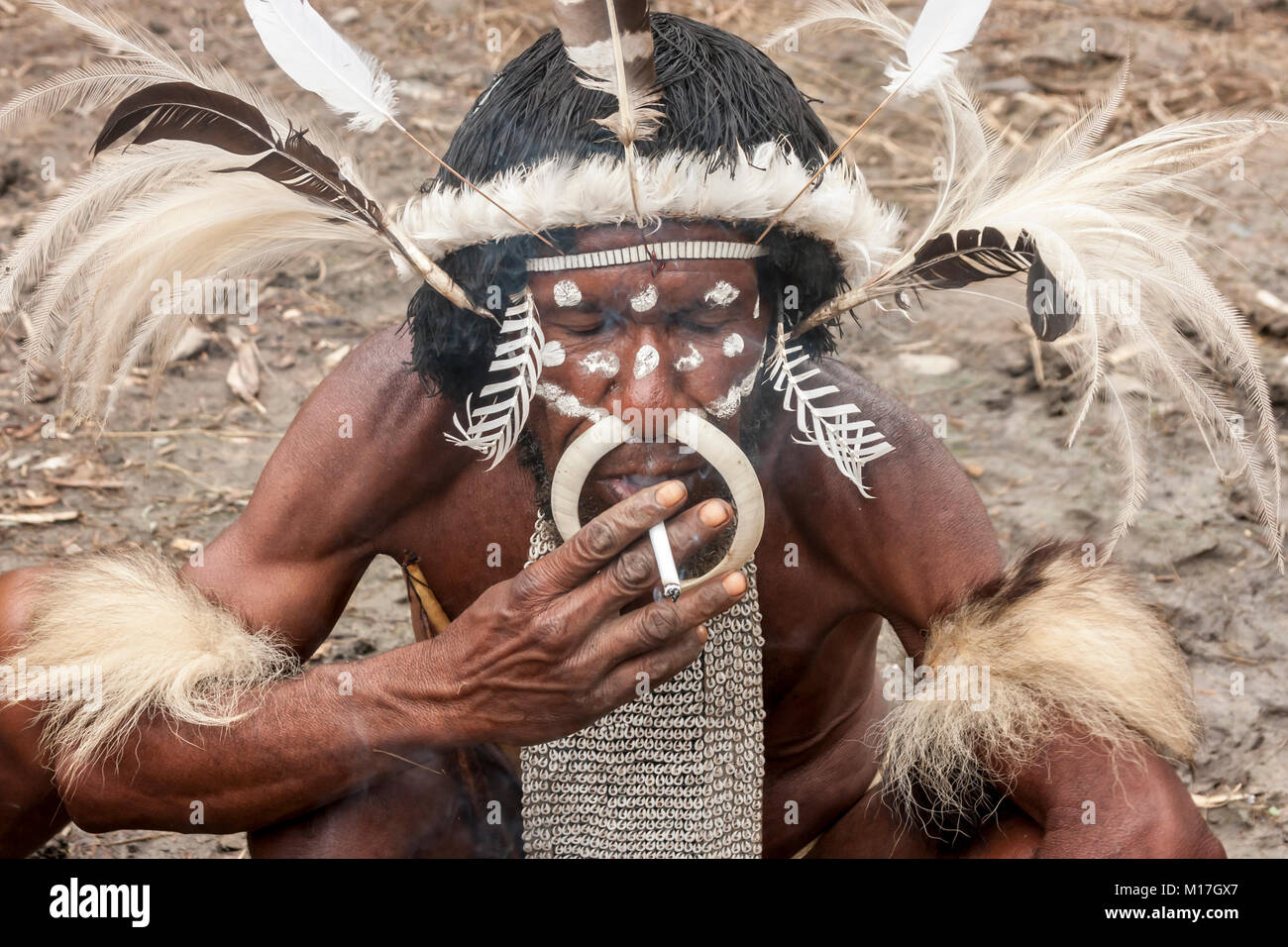 Wamena, Indonesia. The head of the Dani tribe in a traditional dress smoking a cigarette in Dugum Dani Village. - Stock Image