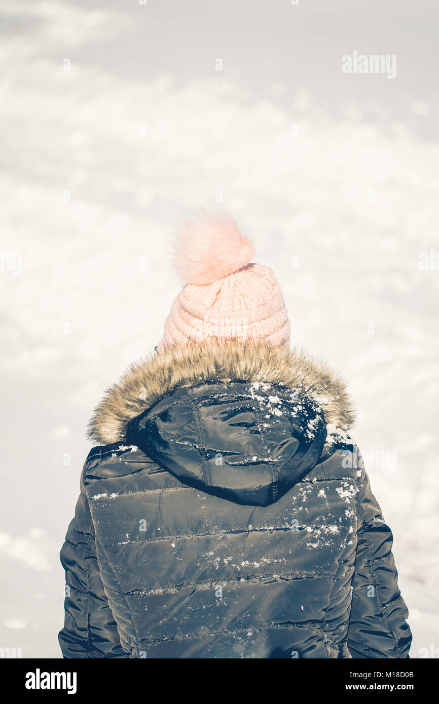 Little girl with a pink hat looking out at freshly fallen snow - Stock Image