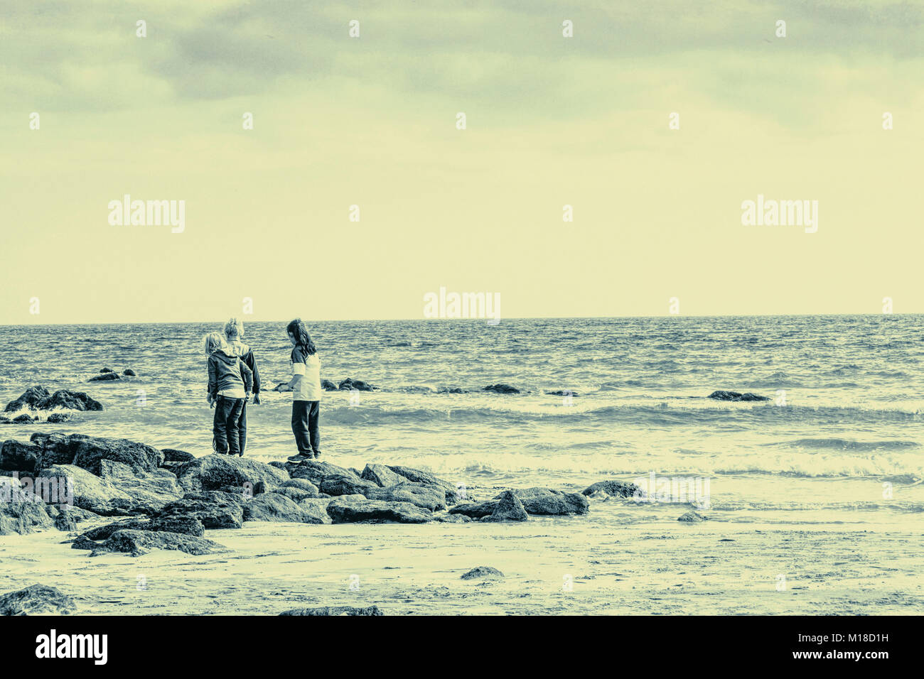 Three children playing at the seaside - Stock Image
