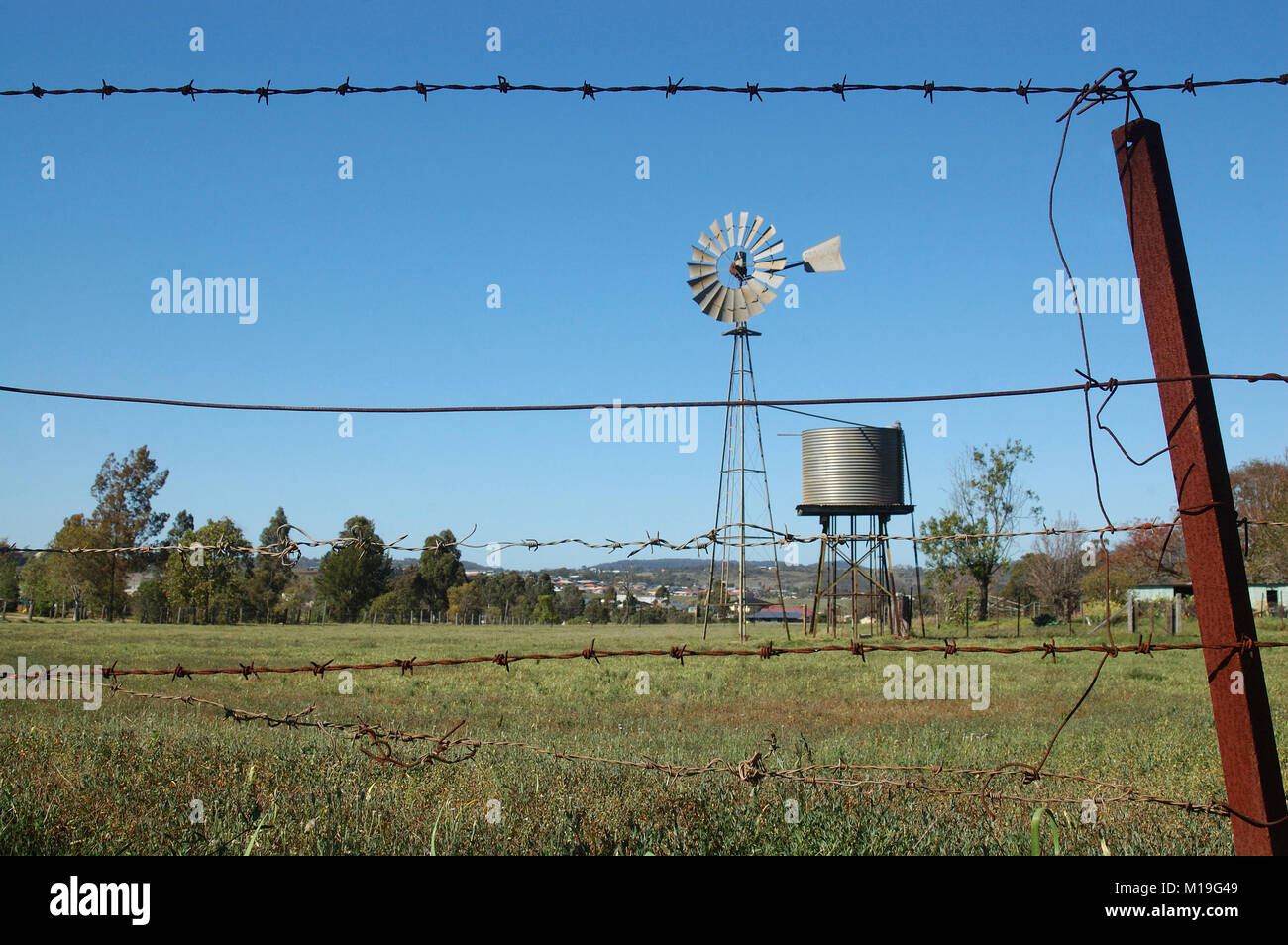 Windmill and tankstand in paddock, Queensland, Australia. Windmills are commonly used for pumping water from bores - Stock Image
