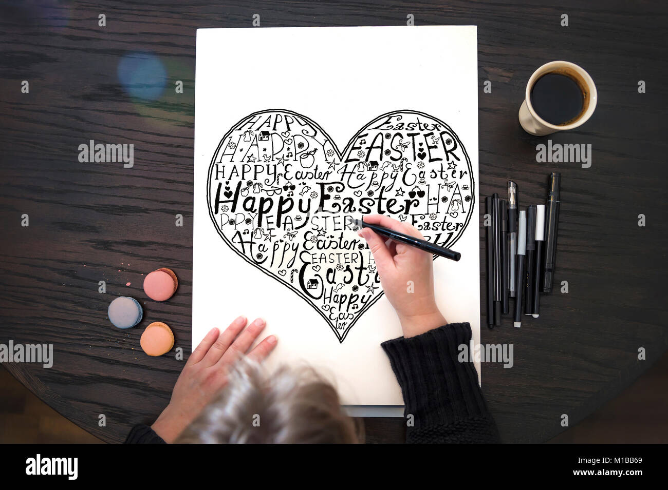 Hand lettering - A woman sits at the table and draws the text Happy Easter on paper - Stock Image