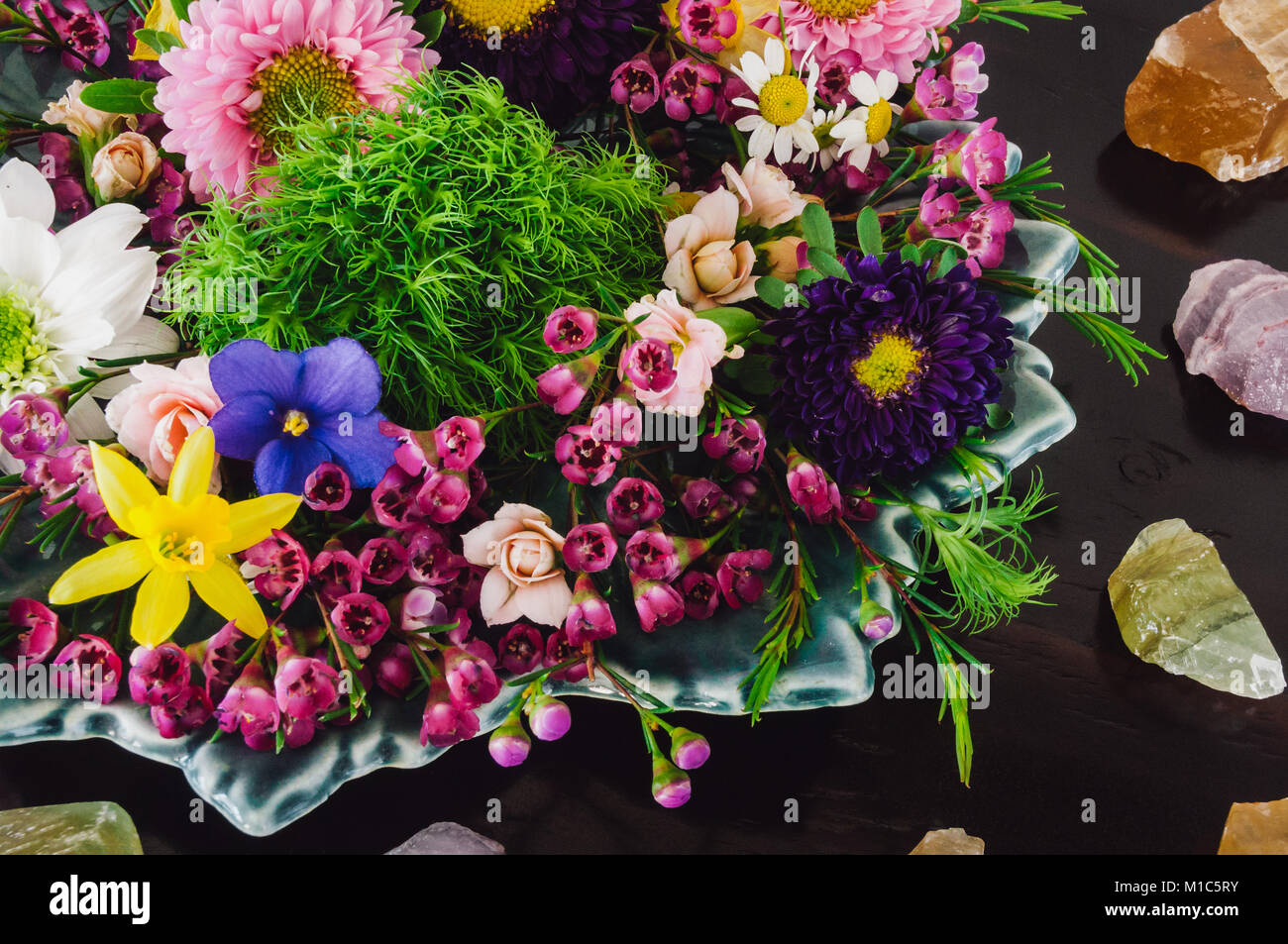 Assorted Spring Flowers on Dark Table with Honey Calcite, Amethyst and Green Calcite - Stock Image