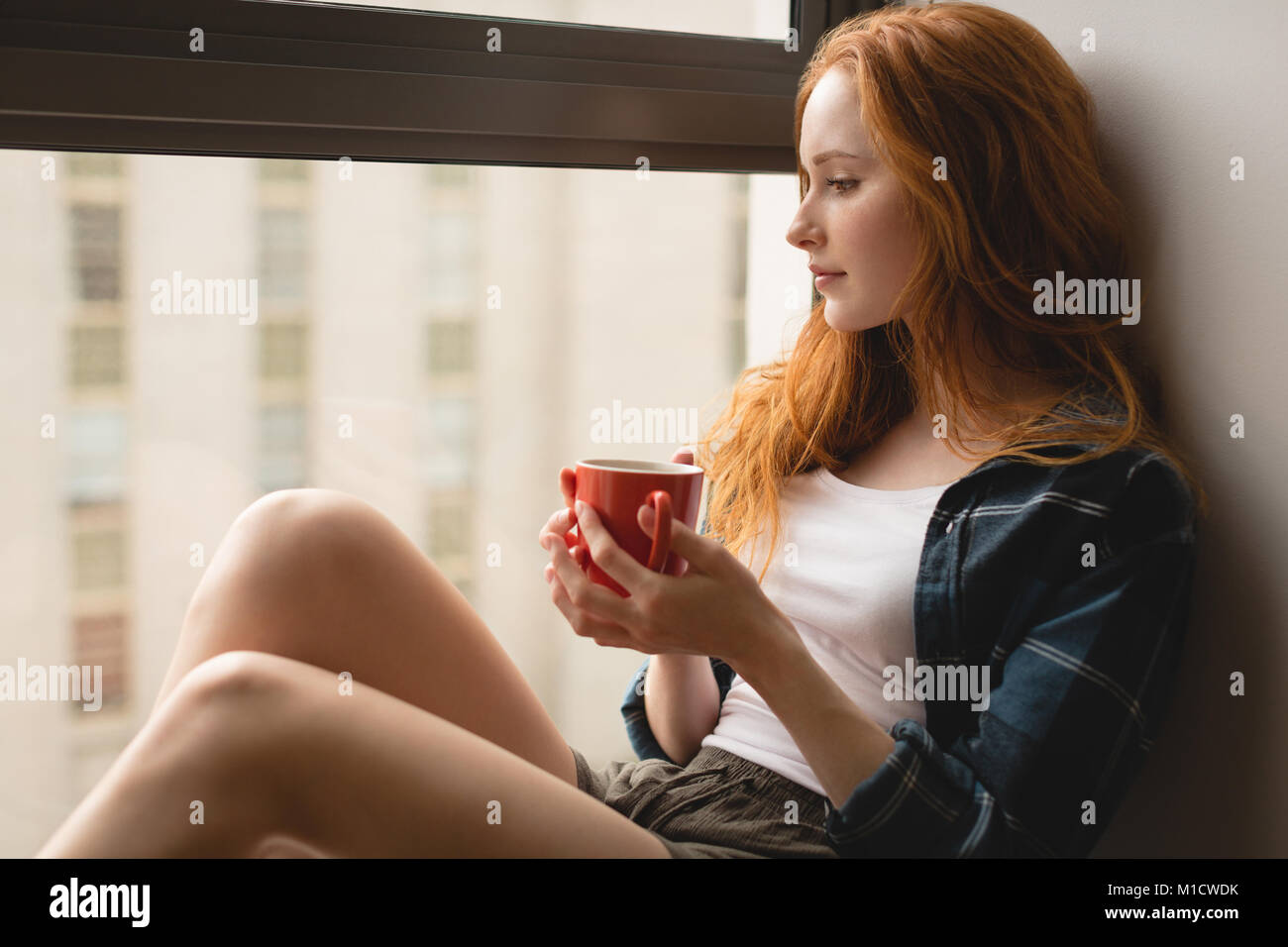 Woman having coffee at home - Stock Image