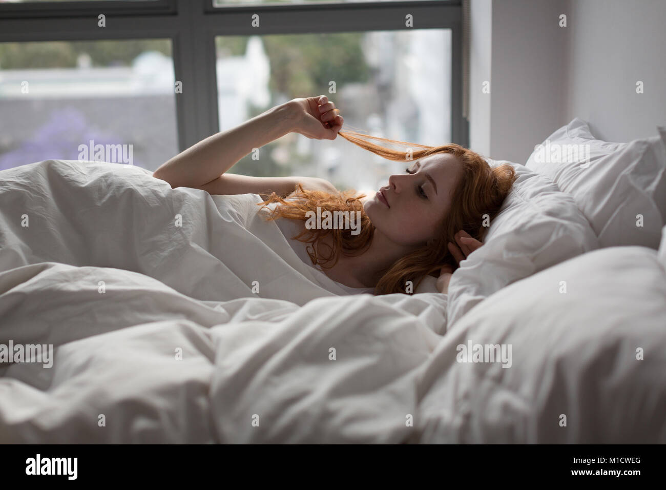 Woman relaxing on bed in bedroom at home - Stock Image