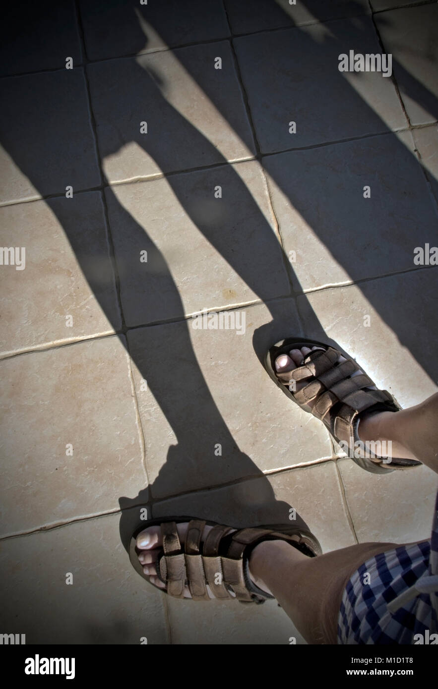 shadow from legs and feet in sandals - Stock Image