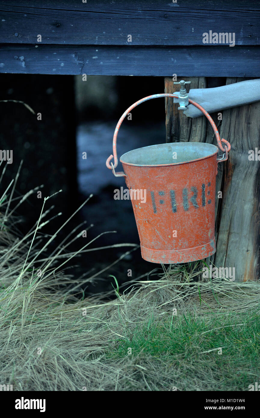 fire bucket hanging outside wooden house - Stock Image