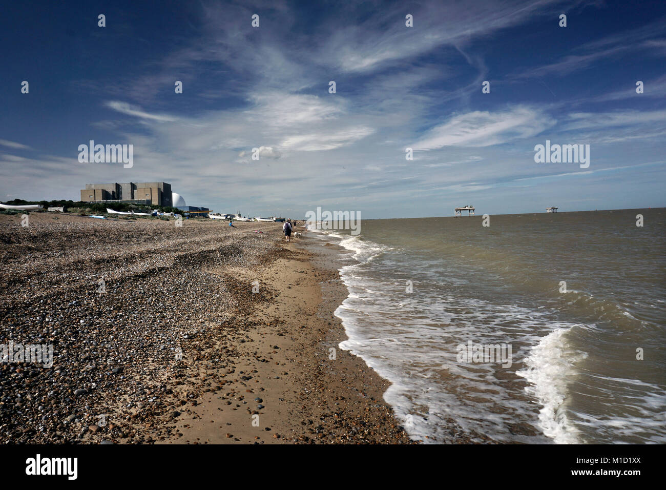 walking past sizewell power station on the beach at sizewell suffolk england uk - Stock Image
