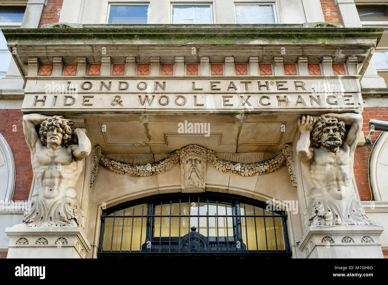 Two classical Atlantes or Telamons support the portico above the entrance to the London Leather, Hide & Wool - Stock Image