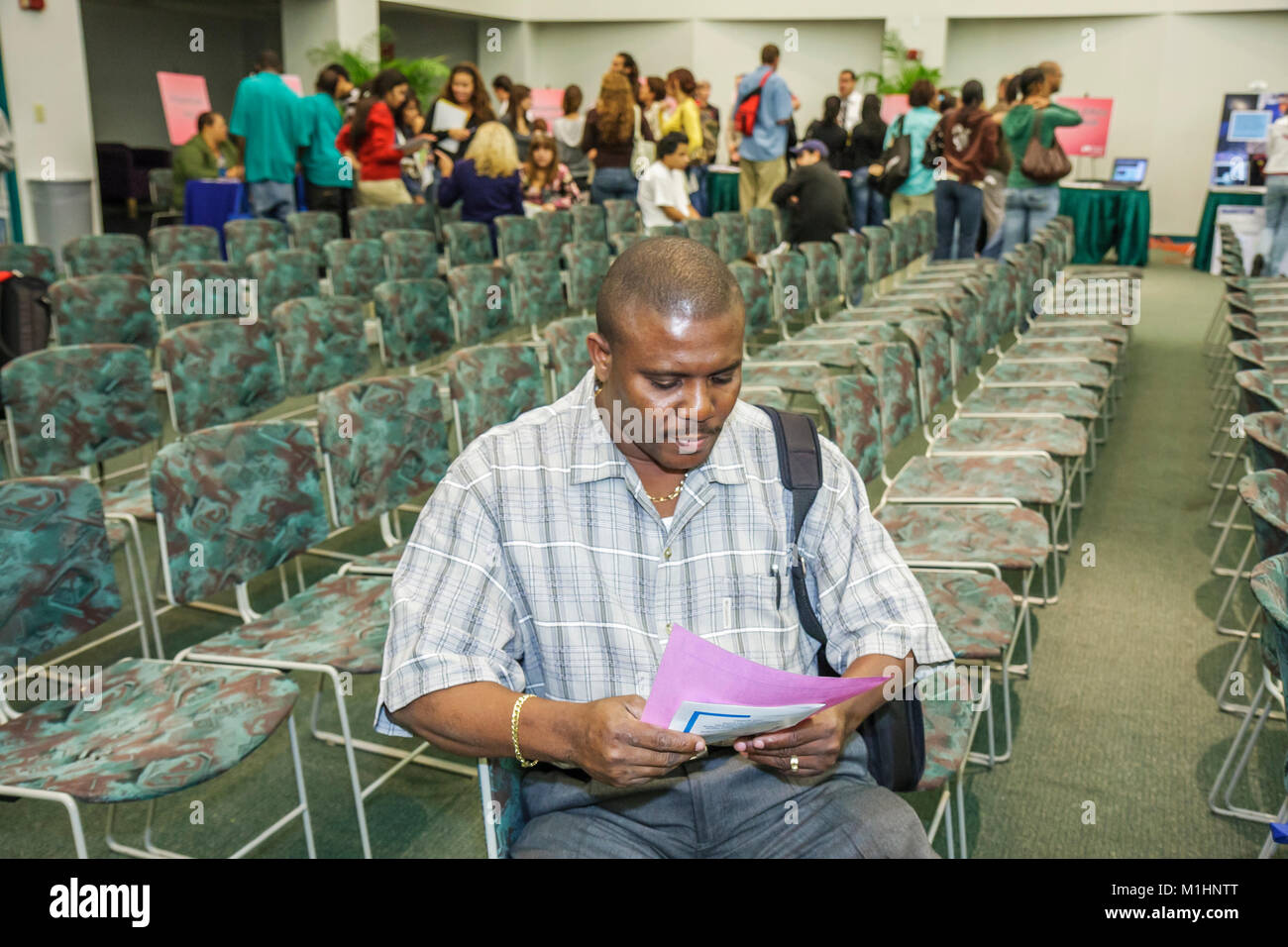 courses recruiter orientation counselor Black man empty chairs rows deciding thinking isolate information - Stock Image