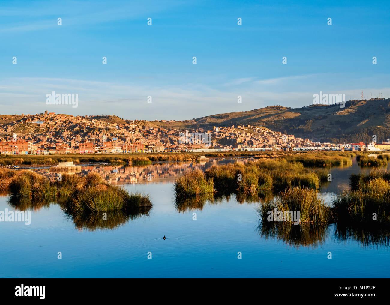 Lake Titicaca and cityscape of Puno at sunrise, Peru, South America - Stock Image