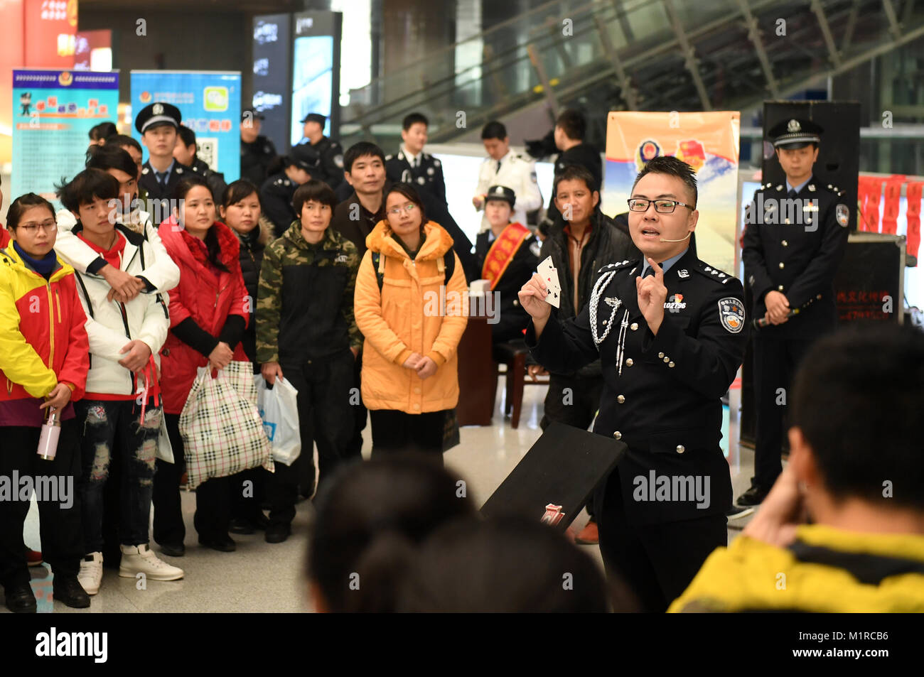 Nanning, China's Guangxi Province. 1st Feb, 2018. A police officer warns passengers of deceitful card tricks - Stock Image