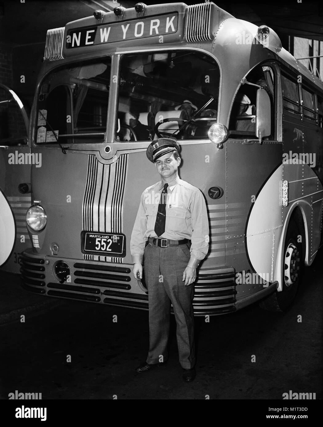 Greyhound Lines Bus Driver Standing next to Bus Headed for New York, Harris & Ewing, 1937 - Stock Image