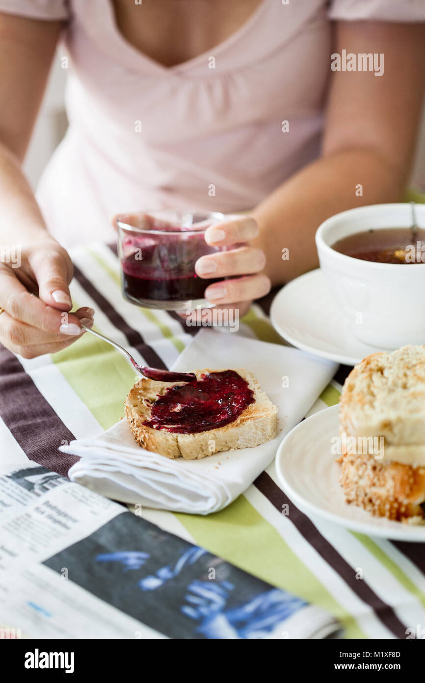 Hands of woman spreading jam on toast - Stock Image