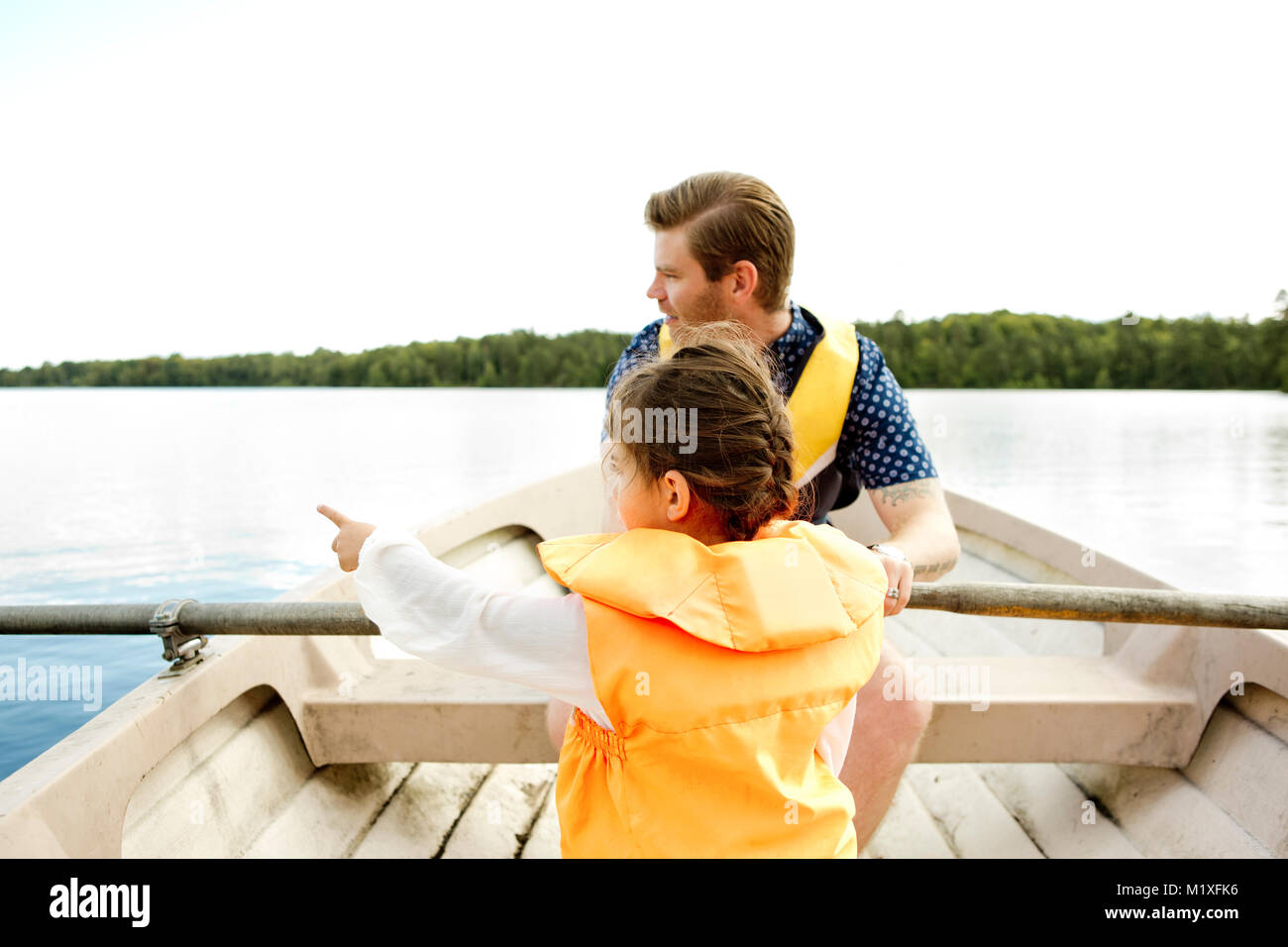 Girl in row boat with her father in Friseboda, Sweden - Stock Image