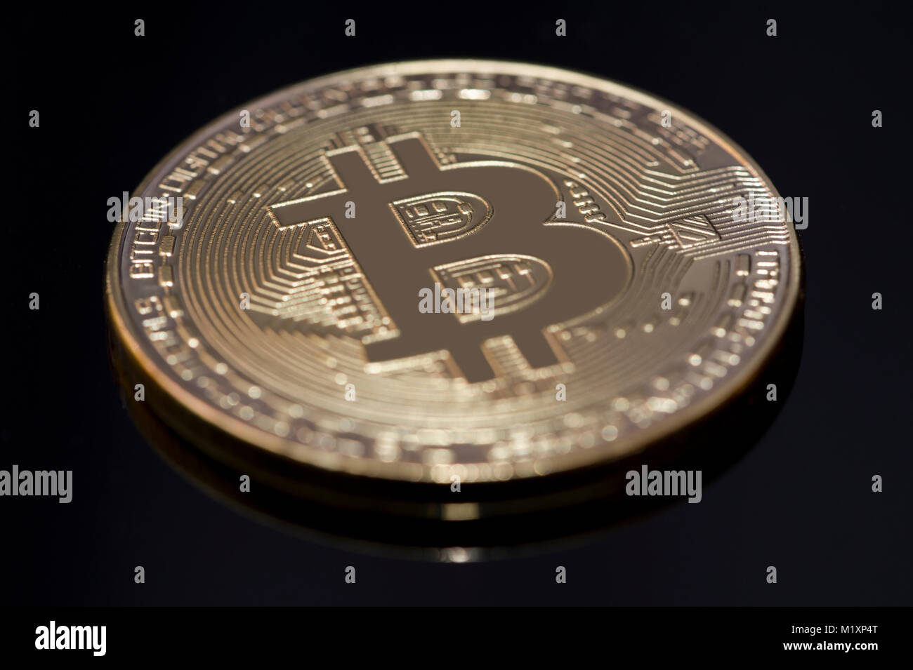 A Gold Bitcoin on a gloss black background - Stock Image