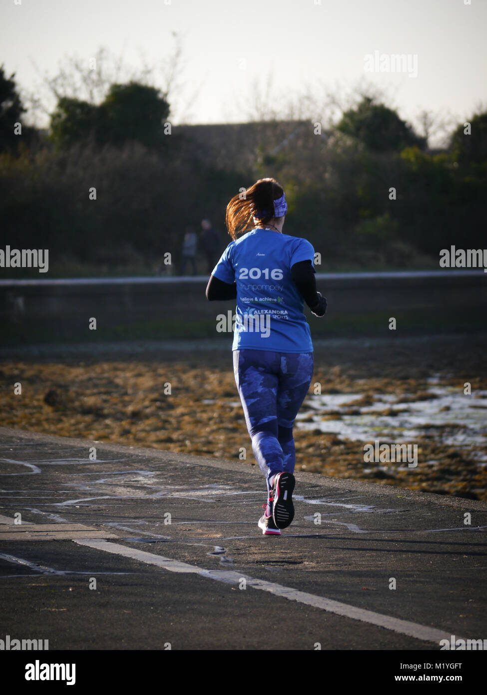 a-young-lady-running-along-a-public-footpath-M1YGFT.jpg