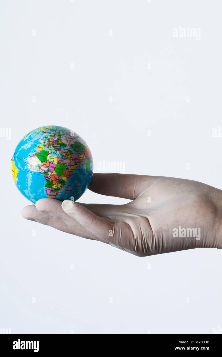 MODEL RELEASED. Person wearing latex glove holding small globe Stock ...