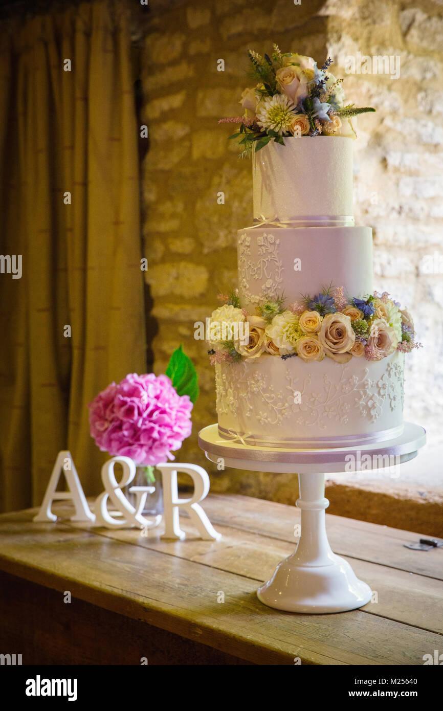 Fresh Flowers On Three Tiered Wedding Cake On Cake Stand Stock Photo