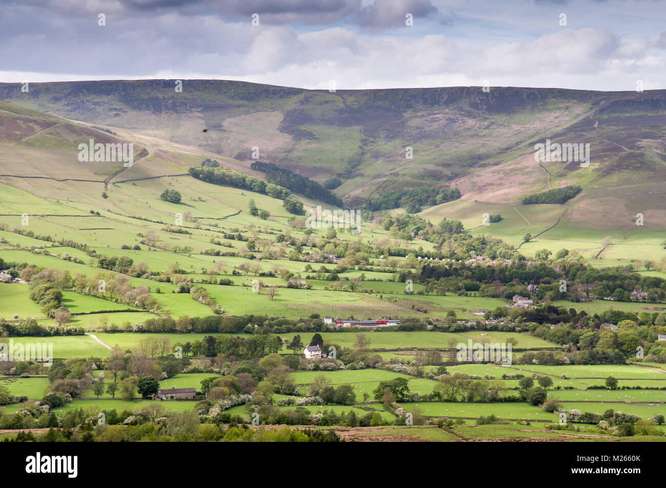 The moorland plateau of Kinder Scout rises above the lush pasture fields of Edale valley in Derbyshire, in England's - Stock Image
