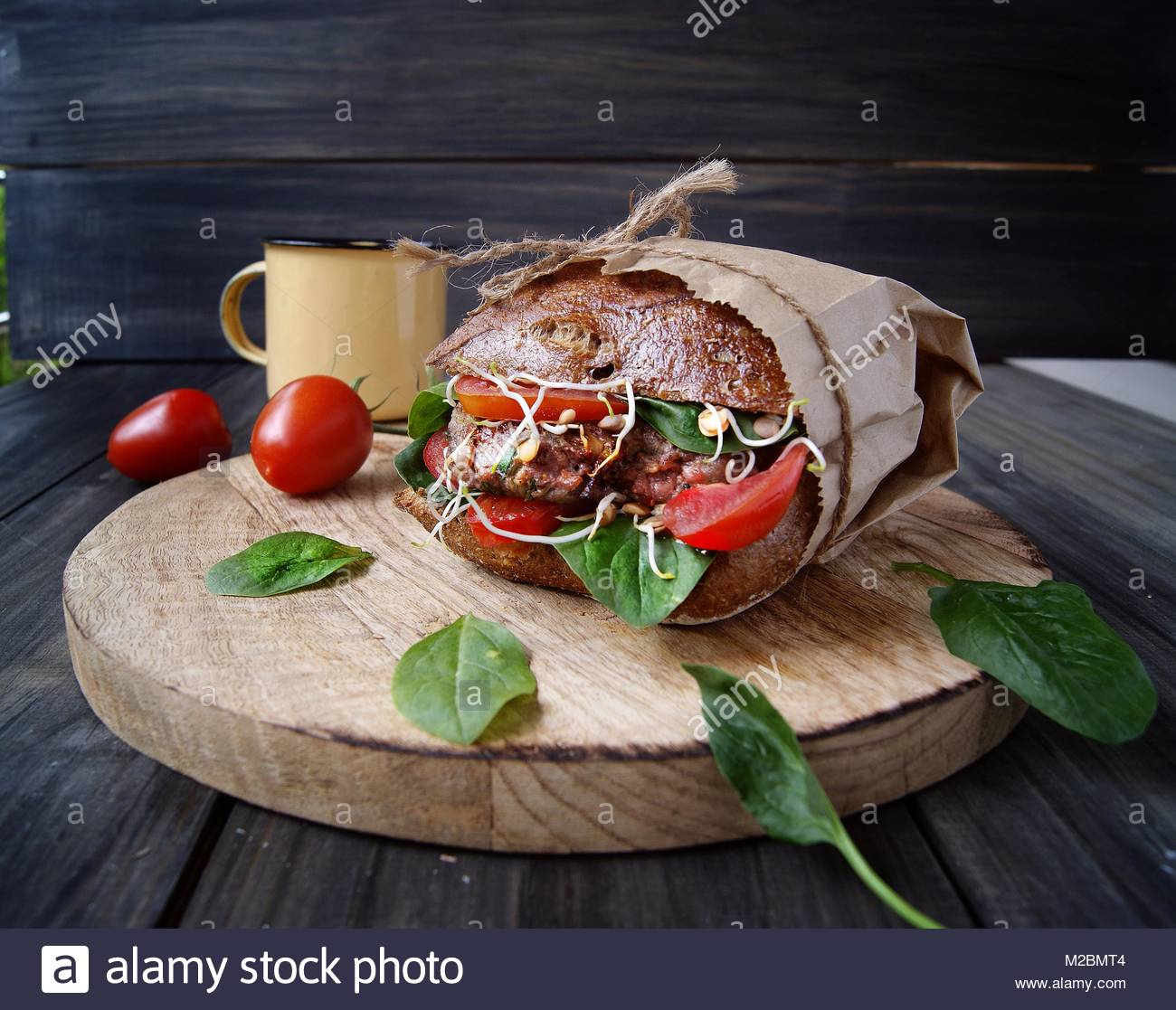 hamburger with black bread and tomatoes on table - Stock Image
